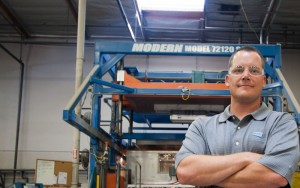 Brian Ray President Company Leadership Standing Arms Crossed Blue Orange Manufacturing Machinery