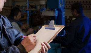Man with clip board in manufacturing facility taking notes